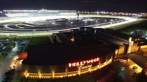 An aerial view of Hollywood Casino at night with the oval of Kansas Speedway visible behind it.